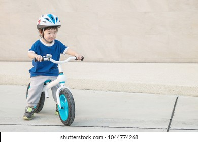 Closeup cute kid ride a bicycle on cement floor at the car park textured background with copy space