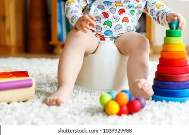 Closeup of cute little 12 months old toddler baby girl child sitting on potty.