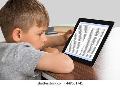 Close-up Of Cute Little Boy Learning Through Digital Tablet