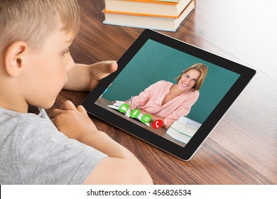 Close-up Of Cute Little Boy Videoconferencing On Digital Tablet In Classroom