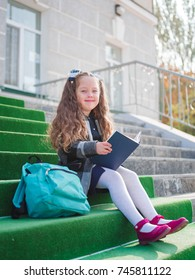 Close-up of a cute little girl with a book in her hands.
