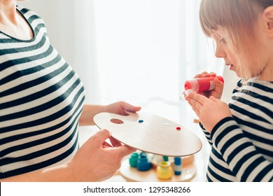Closeup of cute little girl painting with her mother at home