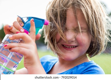 Closeup of cute little girl wincing as she sprays water on her face to cool off during a game break