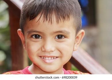 Closeup cute portrait of Asian little boy smiling outdoor
