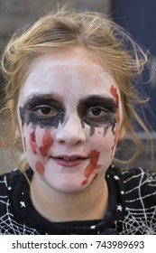 Closeup of cute smiling little blonde girl with zombie makeup and black dress