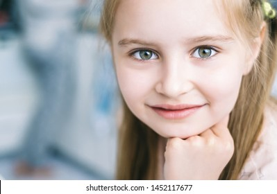 Closeup of cute smoling girl with green eyes looking in camera