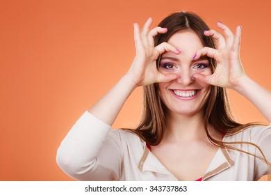 Closeup cute woman looking through imaginary binocular funny looking through fingers simulating glasses orange background