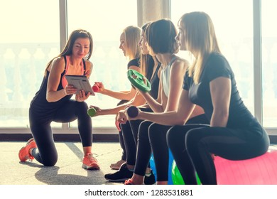 Close-up cute young women in sport wear do exercise with dumbbells in their hands sitting on fitball and listen to fitness instructor with gadget in her hands in gym against light