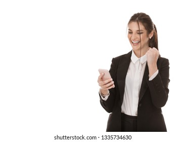 Closeup cutout portrait of a beautiful euphoric woman holding phone and pumping fist jubilation, she just won an online lottery, girl wearing formal black suit, shirt isolated onpure white background