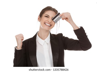 Closeup cutout portrait of a beautiful euphoric smiling woman holding plastic credit card and pumping fist in jubilation, girl wearing formal black suit white shirt isolated on a pure white background