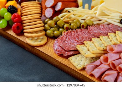 Closeup of cutting board with sliced salami, crackers, green olives, nuts and berries and assorted cheese.