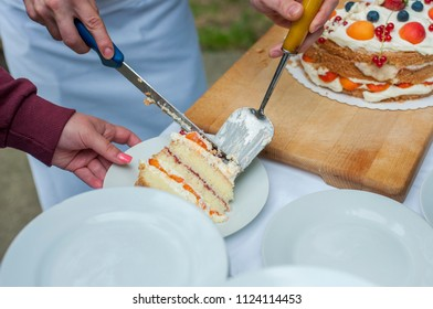 Closeup of cutting the wedding cake. Cutting fruit wedding cake.