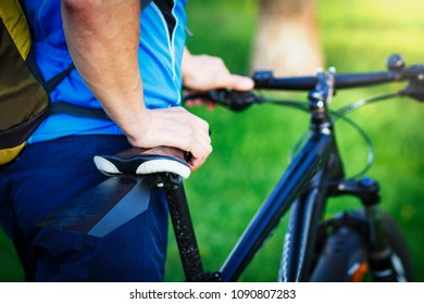 Close-up of cyclist rides bicycle against green park background. Ride bike in the summer. Leisure. Sports and healthy lifestyle concept.