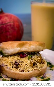 Closeup of Dabeli Indian Dish with a Pomegranate and a Mango Lassi in the Background