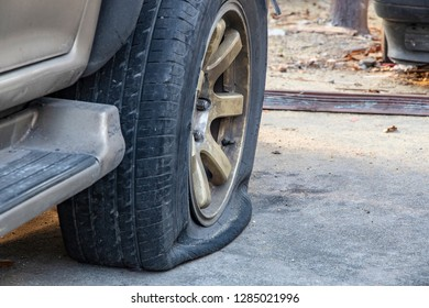 Close-up of damaged flat tire of  car on parking.