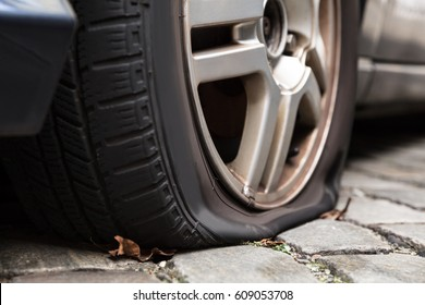 Close-up Of A Damaged Flat Tire Of A Car On The Road
