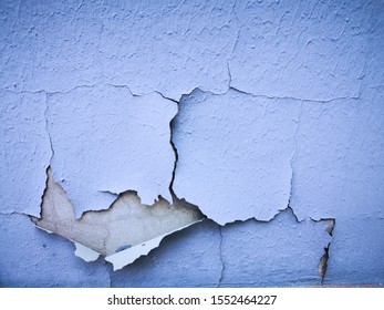 closeup of damaged weathered and paint pealing from blue painted wall
