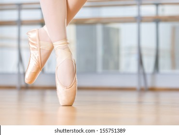 Closeup of dancing legs of ballerina wearing white pointes in the dancing hall