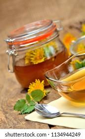 Close-up of dandelion honey, spoon, dandelion head around and full jar in background - vertical photo