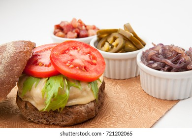 Closeup of dark bread cheeseburger with cheese tomato and aligned side servings of bacon onion cucumber