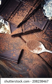 Closeup of dark chocolate and cocoa Powder over spoon over wooden background