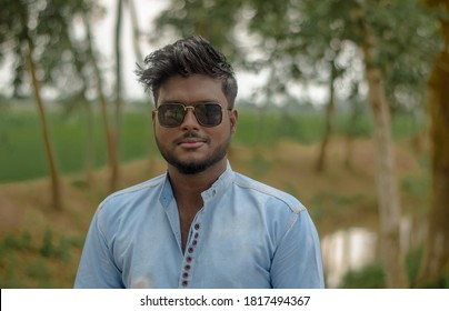 Close-up of dark skinned young man Wearing casual blue shirt. Look straight on camera through black sunglasses. Relax profile pose with smile on face at outdoor.