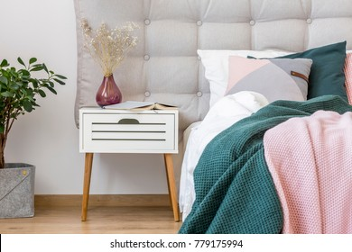 Close-up of dark vase with flowers on white nightstand next to bed with pink and green bedsheets in pastel bedroom interior