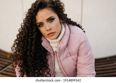 close-up. Dark-haired curly beauty with green eyes and makeupcursive looks heeding while studying something, dressed in warm clothes. High quality photo