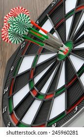 Closeup of dart board with darts.