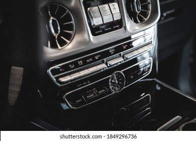 close-up of the dashboard of a luxury car with air conditioning ducts, player, clock and control buttons