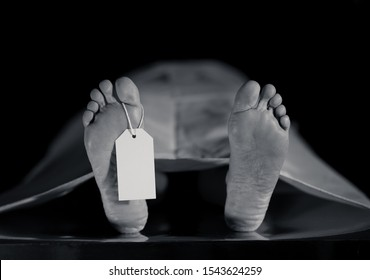 Close-up of dead body feet at morgue or hospital with toe label or information ring and identification blank tag. Cadaver lying on steal table covered with sheet on autopsy table. Death concept.