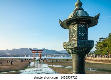 Close-up of a decorated bronze lantern with the famous Torii Gate in depth of field in the background - Itsukushima Shrine.  Miyajima Island, Hiroshima Bay, Japan.