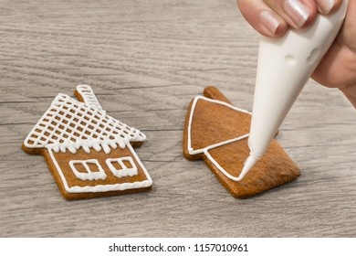 Close-up of decorating sweet gingerbreads in house shape. Detail of a woman's hand and icing bag with frosting while painting the Christmas pastries on a wood background. Xmas or Children's day.