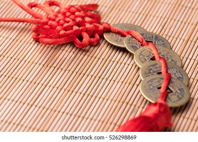 Close-up of decorative Chinese lucky coins with knot on bamboo mat, selective focus