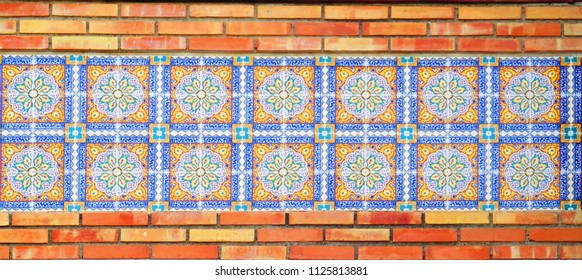 Closeup of decorative Tiles recessed in brick wall in Andalusian village