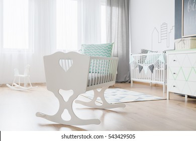 Close-up of a decorative white cradle in a very bright baby room