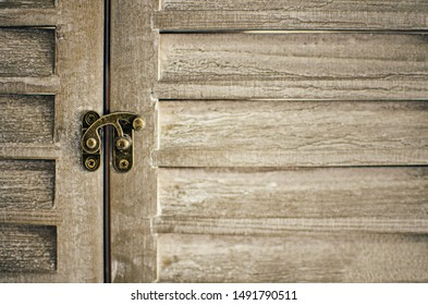 Closeup of a decorative wooden shutter window. Detail of the lock (selective focus) Background.
