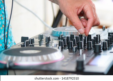Close-up of deejay hand on equipment deck and mixer audio equipment at party.