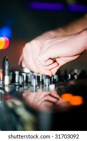 Close-up of deejays hand and turntable, soft focus