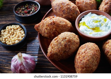 close-up of deep fried kibbeh of ground beef meat mixed with bulgur, stuffed with fried minced meat with pine nuts, spices, garlic and herbs on a clay plate on an old dark wooden table