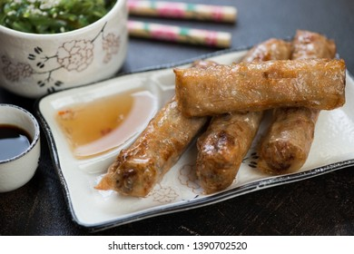 Close-up of deep fried vietnamese spring rolls with dipping sauces and seaweed salad, selective focus