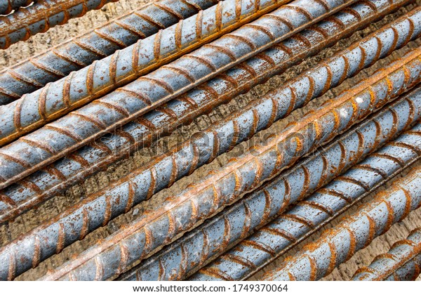 Closeup deformed bar. Rusty deformed bar on cement concrete flooring in construction site. Steel rods or reinforcing background. Rebar picture.