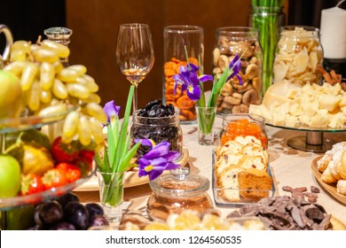Closeup degustation premium cognac with snacks, fresh and dried fruits, pieces parmesan cheese, honeycombs, dark chocolate, cinnamon sticks, biscotti, croissants, flowers, candles