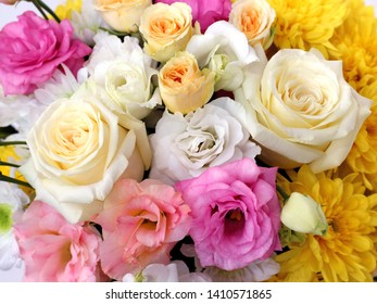 close-up of delicate flowers in a bouquet. yellow roses, pink eustoma, white eustoma, white chrysanthemums, yellow chrysanthemums with blurred background, top view