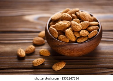 Close-up of delicious almonds in a wooden bowl on a wooden table