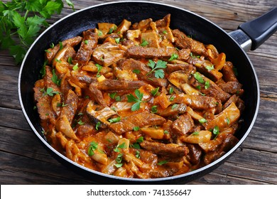 close-up of delicious beef stroganoff - veal strips stewed with porcini in sour cream sauce sprinkled with finely chopped parsley on skillet, authentic recipe,  view from above