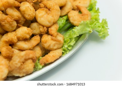 Closeup of delicious deep fried shrimps served with lime wedges and letuce leaves on white plate on white table, blank space for text left, view from above.