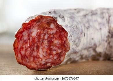 Closeup of a delicious dry sausage on a wooden cutting board