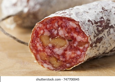 Closeup of a delicious dry sausage with walnuts on wood