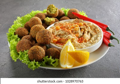 close-up of delicious falafel balls on plate with homemade hummus sprinkled with paprika and olive oil in a bowl, chili peppers and lettuce leaves, authentic recipe, horizontal view from above